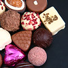 Close up of a selection of luxary chocolates, with a foil wrapped pink heart, which could be for Valentines Day.