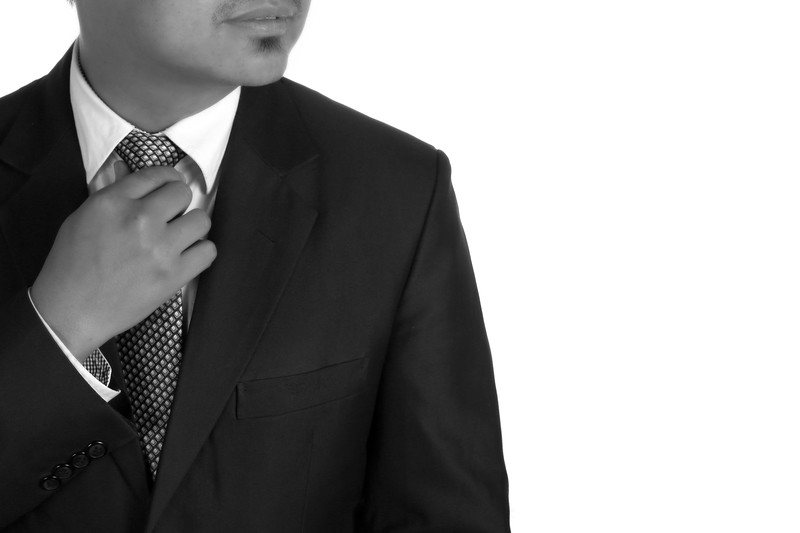Business man adjusting his tie, cropped so face is not visable.