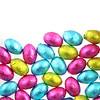 Pile of foil wrapped chocolate easter eggs in pink, blue & lime green with a white background.