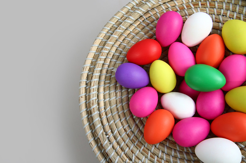 Brightly colored easter eggs, in a straw basket against a grey background.