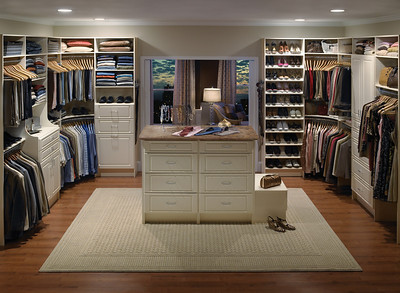 Master bedroom walk-in closet with a center island featuring ClosetMaid MasterSuite in White