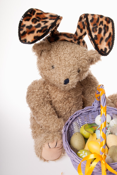 Easter teddy bear dressed in bunny ears with Easter eggs isolated on white background