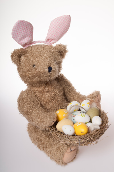 Easter teddy bear dressed up as Easter bunny with bird's nest with Easter eggs isolated on white background