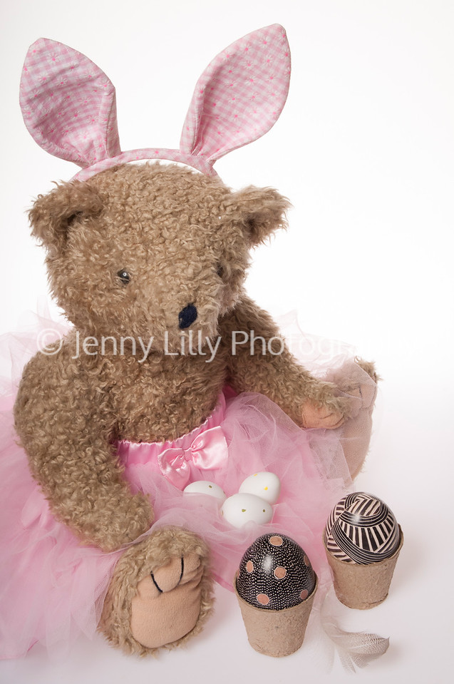 Easter teddy bear dressed as the Easter bunny with Easter eggs isolated on white background