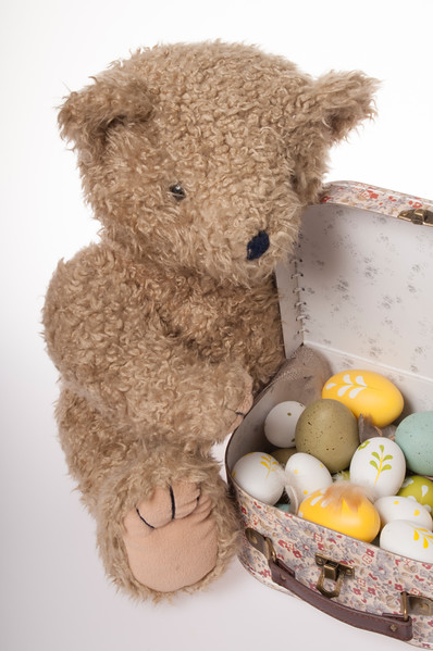 Easter teddy bear with Easter eggs  in a child's suitcase isolated on white background