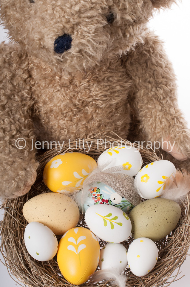 Easter teddy bear with Easter bird's nest with eggs isolated on white background