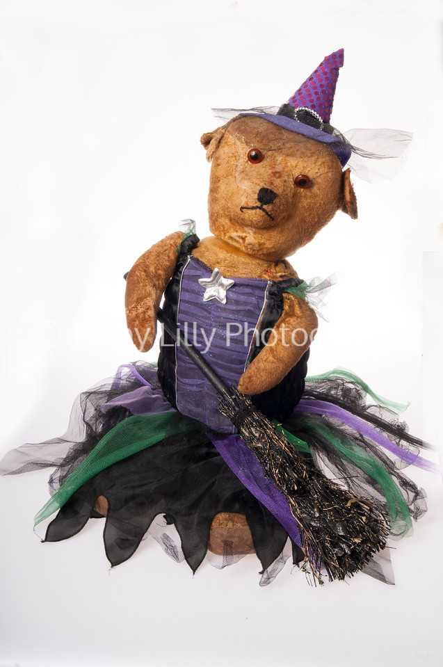 Vintage teddy bear dressed as a Halloween witch isolated on white background