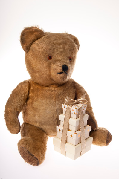 Vintage teddy bear with pile of presents isolated on white background