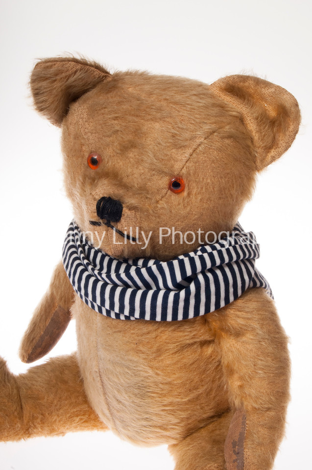 Vintage teddy bear in scarf isolated on white background