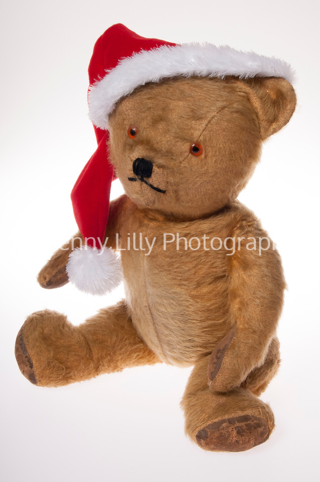 Vintage teddy bear wearing a santa hat isolated on white background