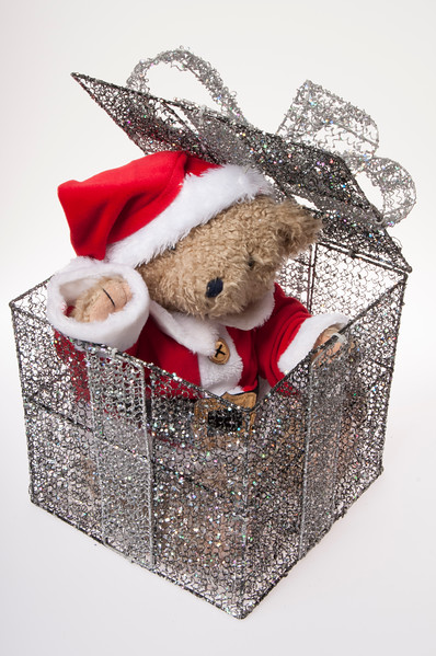 teddy dressed as Santa inside a silver present box, isolated on white background