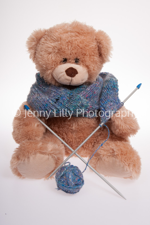 teddy bear knitting a scarf isolated on white background