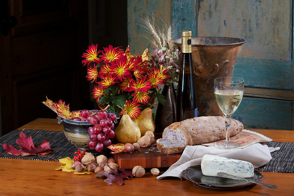 Bread, wine, and cheese still life with fruit and flowers