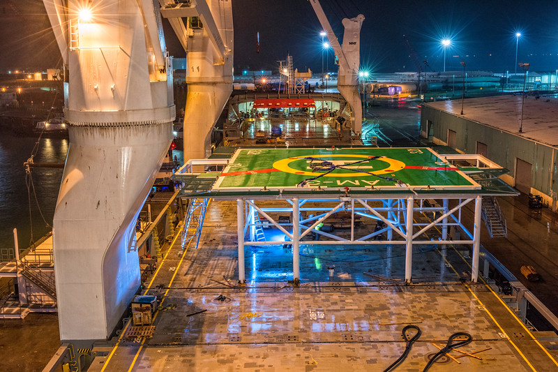 Making up for lost time, heliport platform being secured to ships deck during night operation