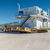 Operator uses joy-stick  controller to maneuver SPMT  transporting crew quarters module to barge