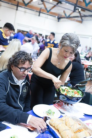 Idalia Campos serving some salad to Martin Tijerino.