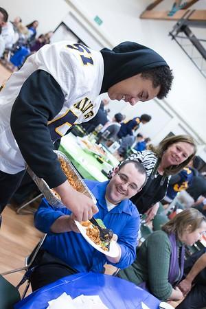 Noah Delaney serving pasta.