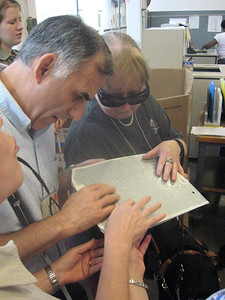 Visitors examine a metal embossed braille plate