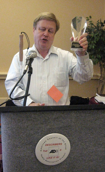 Chris Gray displaying the Barry Levine Memorial Career Achievement Award for Audio Description awarded to Jim Stovall of the Narrative Television Network.