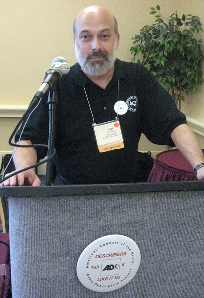 """Joel Snyder, Director of ACB's Audio Description Project, adjourns the Conference--note the display on the podium:  each participant received a pin that reads """"American Council of the Blind, Audio Description Project--Describers Tell It Like It Is"""" surrounding the image of the AD logo, an A and a D with three curved lines emanating from the rounded portion of the D."""