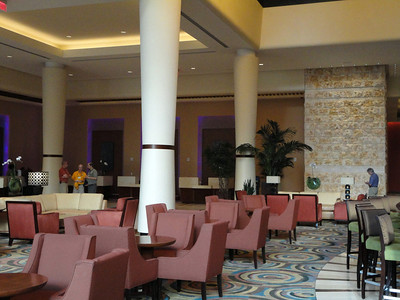 Pictures of the site shared with virtual attendees, along with description:  Phoenix Downtown Sheraton lobby--The high-ceilinged space—perhaps as high as a two-story building—has four white, tapered columns supporting the ceiling; a row of arm chairs in dark pink upholstery is featured with sets of chairs surrounding small tables; at right, stools are arrayed in a curve around a bar.  In the rear, lush foliage is just to the left of a stone, chimney-like façade.