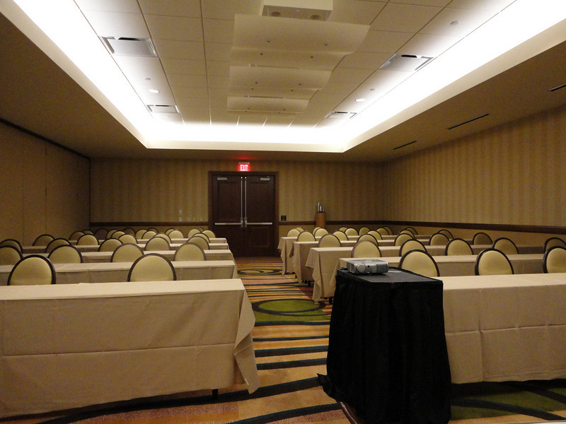 "Our meeting room: ""Ahwatukee A.""  About the size of one-half of a tennis court, long tables and chairs are arrayed horizontally in two sets of five rows with an aisle between the two banks of chairs and tables.   Additional seating is at the rear of the space—on either side of double exit doors.  All together, seating for about 60 is available.  In the foreground, at the front of the aisle, a projector rests on a rectangular, black-cloaked projection table."