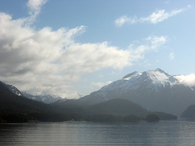 Off the southwest coast of British Columbia-Panorama #3 of 7, left to right: a sweeping vista of a snowy mountain range swooping up and curving low