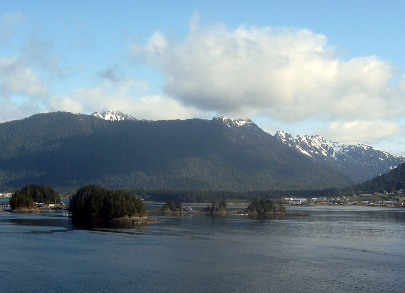 Off the southwest coast of British Columbia-#2:  puffy white clouds hover above a mountain range, rising from the broad expanse of the Pacific Ocean