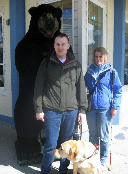 Matthew, Buddy, and Jennie pose with a black bear on a Sitka byway