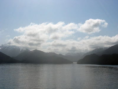 Off the southwest coast of British Columbia-Panorama #7 of 7, left to right: a sweeping vista of a snowy mountain range swooping up and curving low