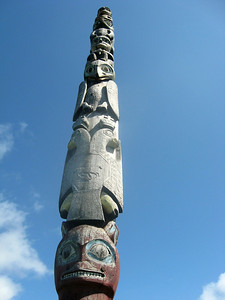 A totem pole is  tall against a blue sky at Totem Square