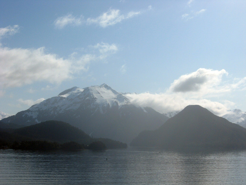 Off the southwest coast of British Columbia-Panorama #4 of 7, left to right: a sweeping vista of a snowy mountain range swooping up and curving low