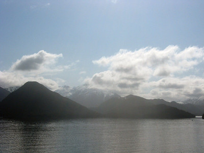 Off the southwest coast of British Columbia-Panorama #6 of 7, left to right: a sweeping vista of a snowy mountain range swooping up and curving low