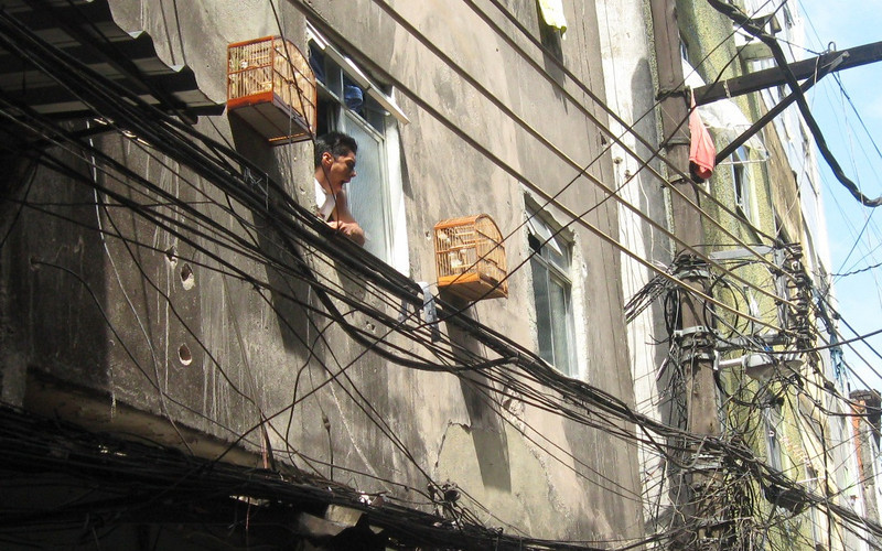 Residents keep pets--often birds in wood cages mounted outside windows.