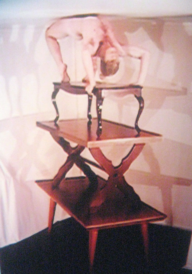"A photo of a photo--a contortionist ""bending over backwards"" atop a table atop a table atop a table."