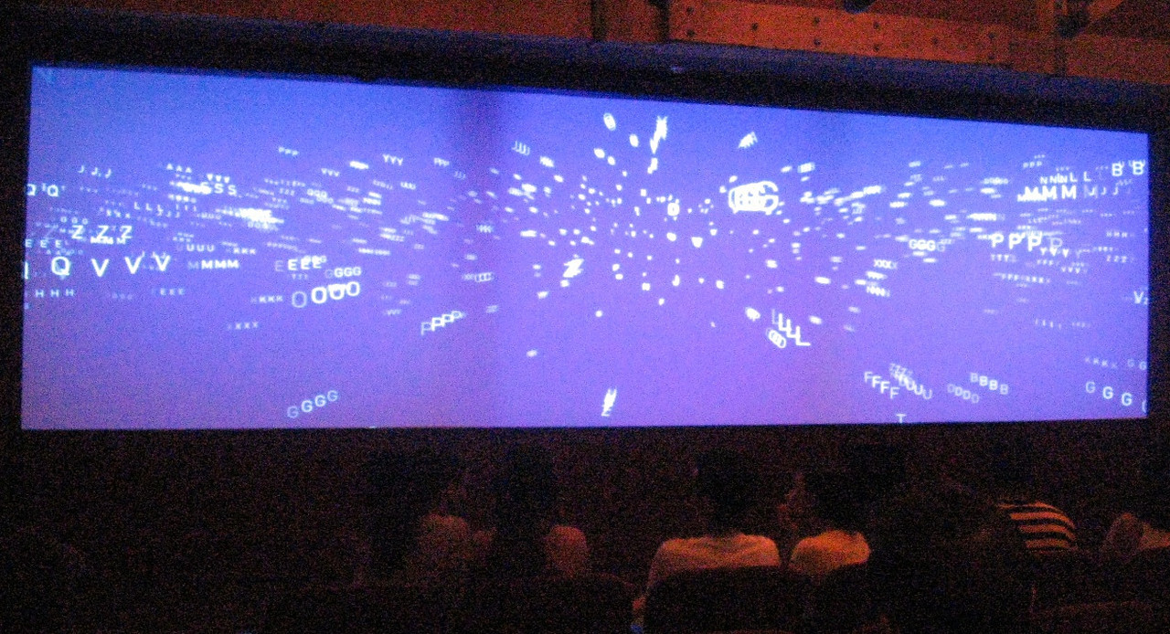 At the end of one floor of exhibits, visitors are led into darkened room with seating on all four sides.  A film begins by featuring letters rushing toward the center of a blue screen as though being pulled together by a massive gravitational force.