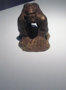 A tiny piece, a man crouched on over-sized hands and feet.