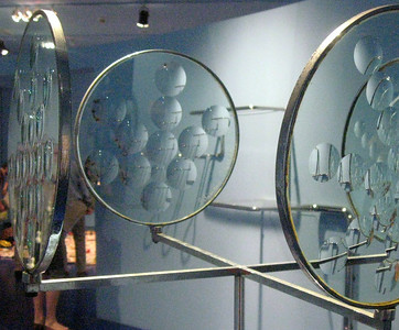 Four hoops of glass lenses positioned at the ends of a metal X.