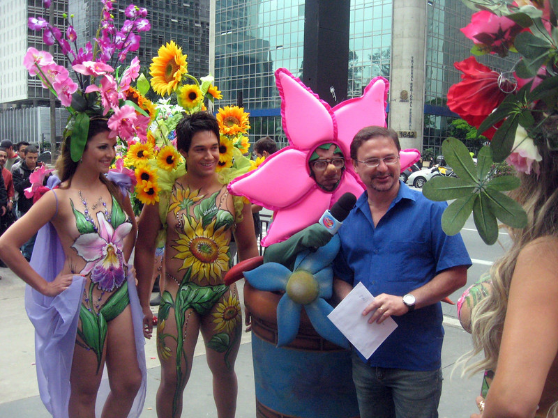 Men and women, clothed only with shoes and headgear with flowers ... and body paint, layered strategically!     What's that guy staring at?