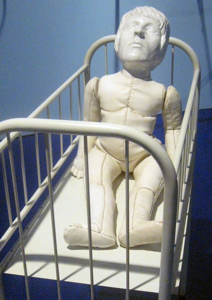 """On to the MAM:  the exhibit """"Jardim de infancia"""" (Kindergarten) includes a variety of works from the museum's permanent collection.  This work features a stuffed doll, adult head on the body of a child doll, resting within a crib."""