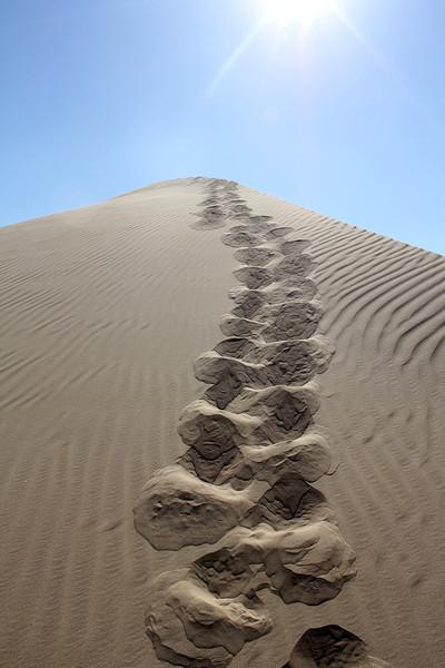 Footprints in sand dunes in California.