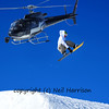 snowboarder performs a high jump while being filmed from a helicopter equiped with a front mounted steady cam.