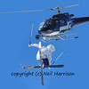 a girl ski jumper performing a high jump being filmed by a team in a helicopter
