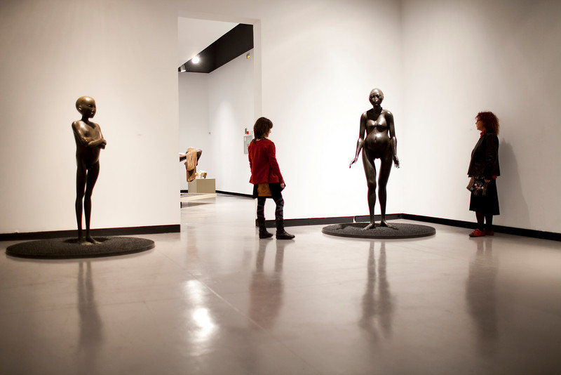 Women looking at bronze sculptures by the Dutch artist Cornelis Zitman (born in 1926), exhibited in Santa Ines gallery, Seville, Andalusia, Spain