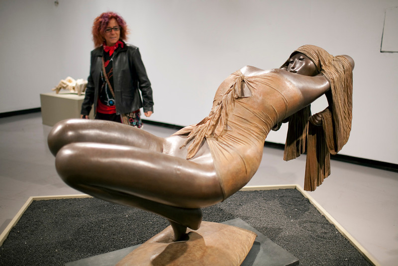 Woman looking at a bronze sculpture by the Dutch artist Cornelis Zitman (born in 1926), exhibited in Santa Ines gallery, Seville, Andalusia, Spain