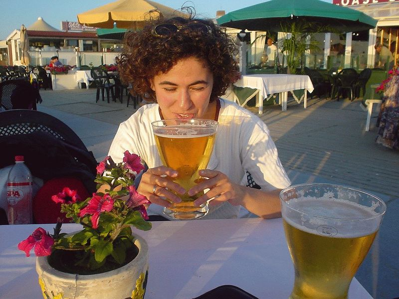 Tijen having a *large* beer at beach club Oase.