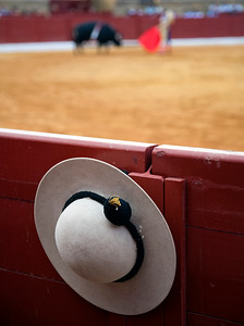 Iconic image of bullfighting. On the foreground, a castoreno (the picador's hat), hanging on the barrier, and, on the background, the bullring itself with bullfight action. Espartinas, province of Seville, Spain, 8th October 2006