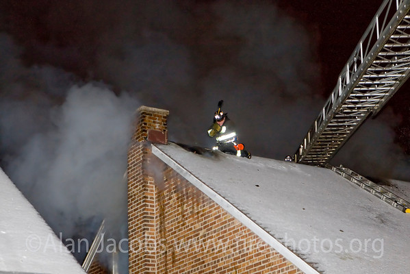 """""""Making the roof"""" at a working still alarm at 11128 S. Ave. """"C"""" in Chicago; a 2 story ordinary, 25X30. Companies responding: E104; T61, 34, 17; 23rd, 24th  Battalion Chiefs; TL 34, & RIT (rapid intervention team),  Sq 5 (recalled).<br /> <br /> Winter cold, slippery, still they are up there riding it like a rodeo bronco, """"venting the roof"""", that is getting holes in it to release heat from this 2nd floor fire. """"In firefighting, ventilation refers to the tactic of creating a draft with an opening above or opposite the entry point so that heat and smoke will be released, permitting the firefighters to find and attack the fire. If a large fire is not properly ventilated, not only will it be much harder to fight, but it could also build up enough poorly burned smoke to create a smoke explosion, or enough heat to create a flashover. Contrarily, poorly placed or timed ventilation may increase the fire's air supply, causing it to grow and spread rapidly."""""""