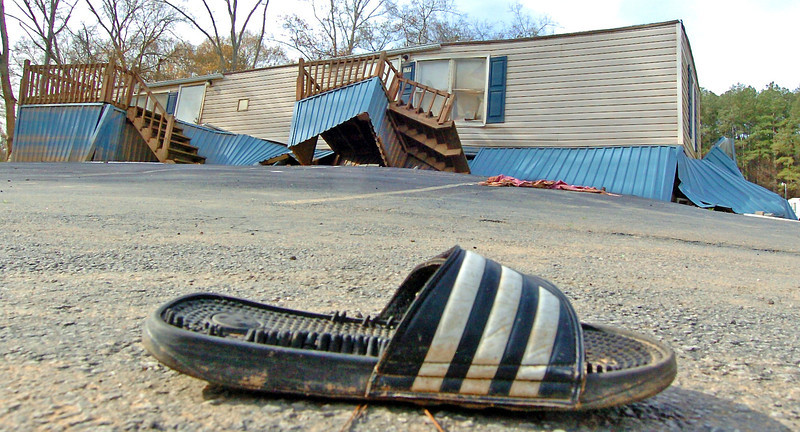A lone sandal left by flood waters sits in the middle of the street surrounded by destroyed and condemed mobile homes.