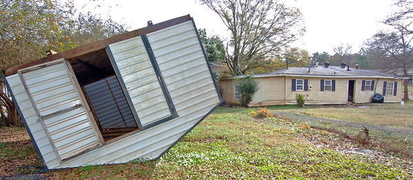 Storage shed ripped from its foundation and washed against trees in floodwaters that were over the roof of the house.